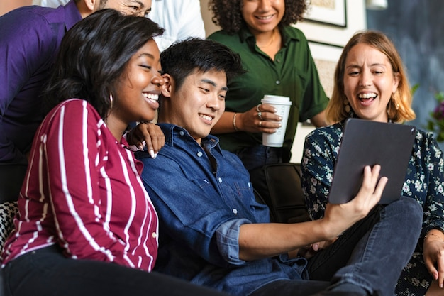 Gruppe verschiedener geschäftsleute, die sich gemeinsam einen inhalt auf einem digitalen tablet ansehen