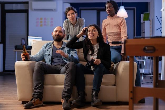 Gruppe verschiedener kollegen, die das spiel mit der vr-brille auf dem konsolenfernseher verlieren, während sie den joystick-controller verwenden. multiethnisches team, das spaß bei der fröhlichen feier im innenbereich hat