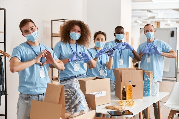 Gruppe verschiedener menschen, die blaue einheitliche schutzmasken und handschuhe tragen, die liebesherzzeichen zeigen