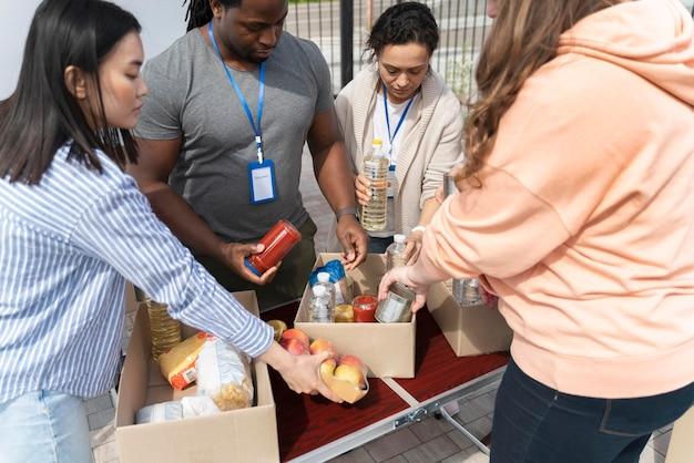 Gruppe verschiedener menschen, die sich ehrenamtlich bei einer tafel für arme menschen engagieren