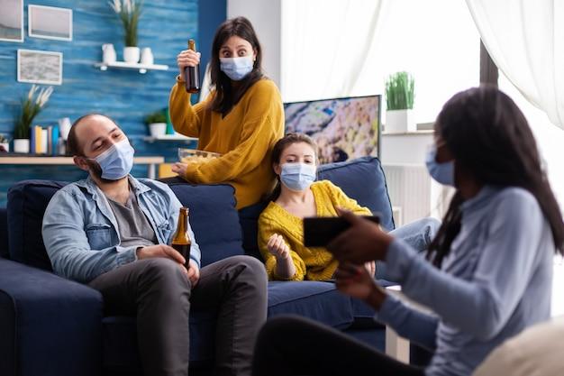Gruppe verschiedener menschen, die sich videos auf dem smartphone im wohnzimmer ansehen und soziale distanzierung mit gesichtsmaske als prävention während des globalen ausbruchs mit coronavirus halten.