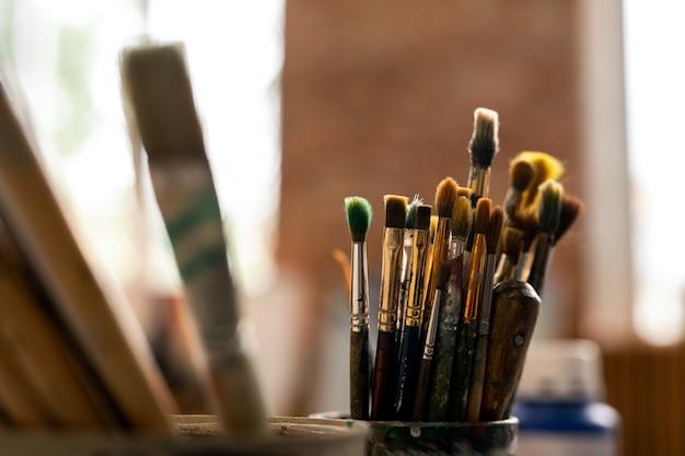Gruppe verschiedener pinsel für professionelles malen am arbeitsplatz des künstlers im atelier der kunst Premium Fotos