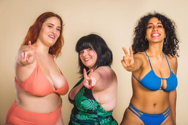 Gruppe von 3 übergroßen frauen, die im studio posieren