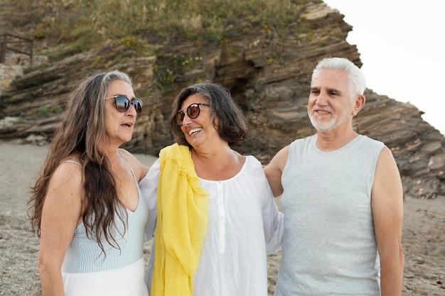 Gruppe von älteren freunden, die zeit zusammen am strand verbringen