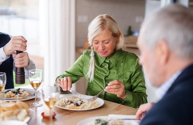 Gruppe von älteren freunden, die zu hause eine dinnerparty genießen und essen.