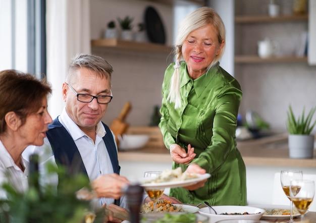 Gruppe von älteren freunden, die zu hause eine dinnerparty genießen.