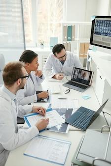 Gruppe von ärzten, die am tisch sitzen und während der online-konferenz beim treffen mit ihrem kollegen sprechen