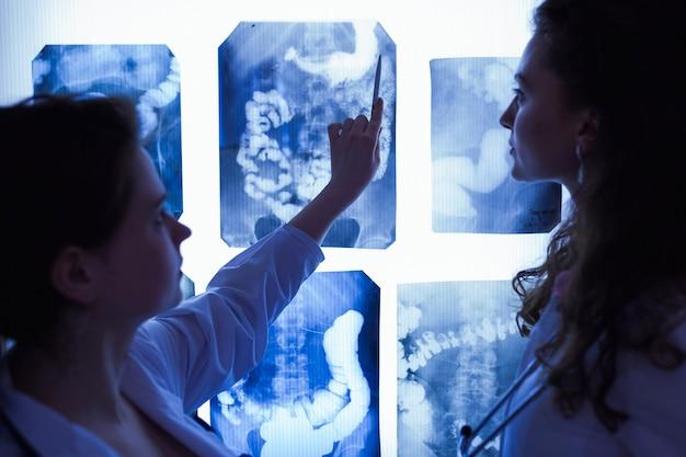 Gruppe von ärzten, die die abschnitte des gehirns untersuchen. das konzept der gesundheitserziehung. schüler im klassenzimmer mit röntgenstrahlen