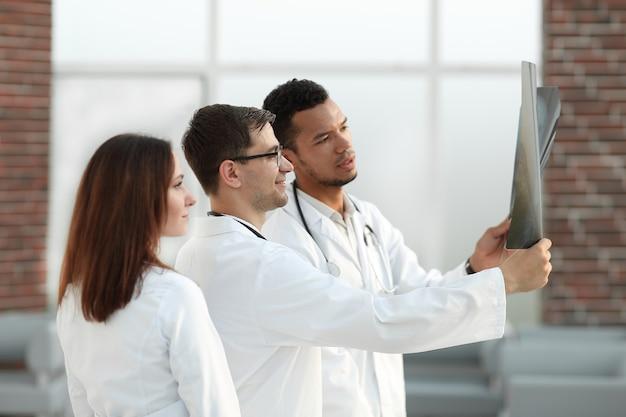 Gruppe von ärzten, die die röntgenaufnahme des patienten besprechen. das konzept der gesundheit