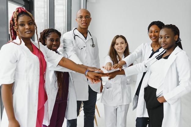 Gruppe von ärzten, die hände in der klinik zusammenstellen.