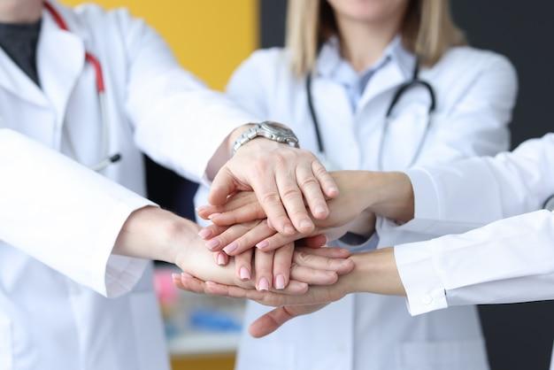 Gruppe von ärzten, die ihre hände in der nahaufnahme der klinik zusammensetzen. teamwork im medizinkonzept