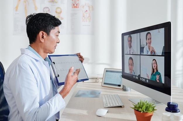 Gruppe von ärzten, die online-konferenz haben und kardiogramm des patienten diskutieren