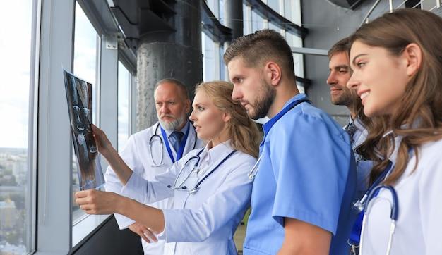 Gruppe von ärzten, die röntgenstrahlen in einem krankenhaus überprüfen.