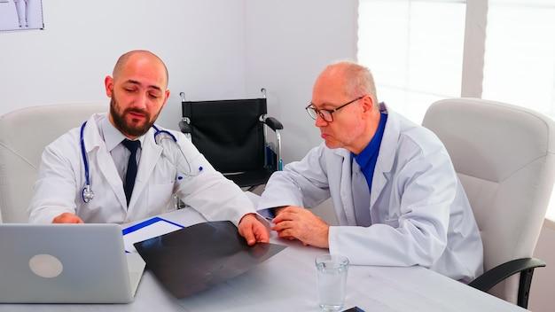 Gruppe von ärzten, die über die radiographie der wirbelsäule eines patienten diskutieren, der seine entwicklung im konferenzraum des krankenhauses analysiert. radiologe arzt im gespräch mit kollegen über symptome und behandlung