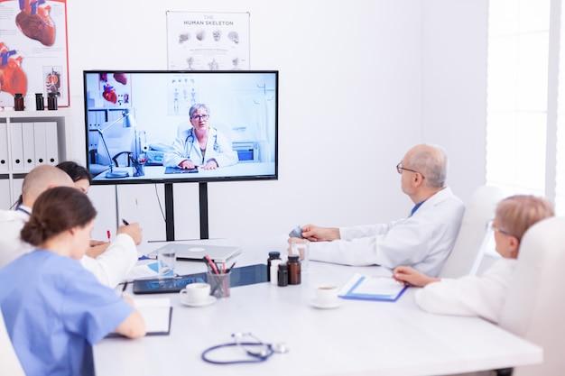 Gruppe von ärzten, die während des videoanrufs im konferenzraum medizinischen experten zuhören. medizinpersonal, das das internet während des online-meetings mit einem erfahrenen arzt nutzt, um fachwissen zu erhalten.