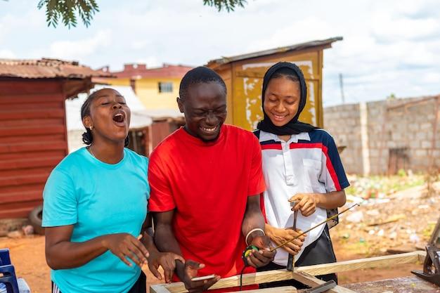 Gruppe von afrikanern, die aufgeregt sind über das, was sie auf ihrem handy gesehen haben