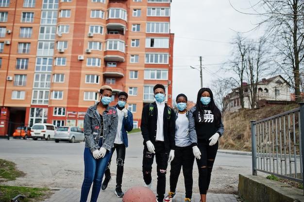 Gruppe von afrikanischen teenagerfreunden gegen leere straße mit gebäude, das medizinische masken trägt, schützen vor infektionen und krankheiten coronavirus-virus-quarantäne.