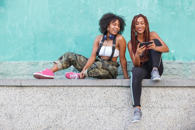 Gruppe von afroamerikanischen frauen, die technologie auf der straße verwenden