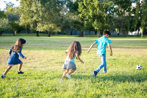 Gruppe von aktiven kindern, die fußball auf gras im stadtpark spielen. volle länge, rückansicht. konzept für kindheit und outdoor-aktivitäten