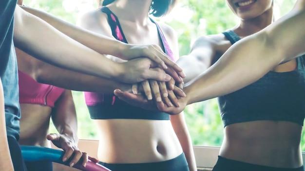 Gruppe von aktiven menschen hand für einheit im fitnessstudio