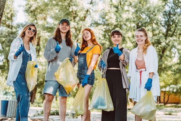 Gruppe von aktivistenfreunden, die plastikmüll am strand sammeln. jungs zeigen daumen hoch.