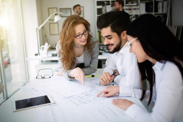 Gruppe von architekten und geschäftsleuten, die zusammenarbeiten und ein brainstorming durchführen