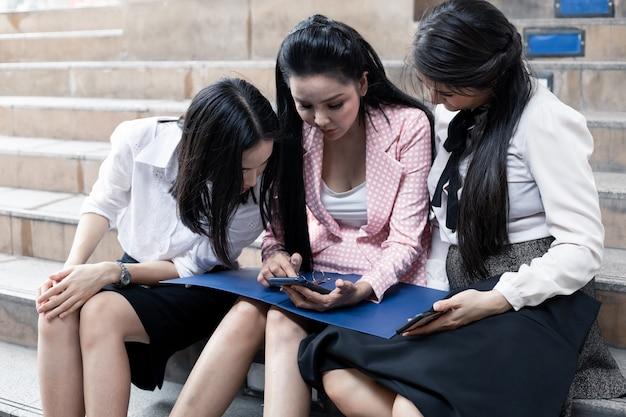 Gruppe von asiatischen geschäftsfrauen, die auf treppen sitzen und arbeitsinformationen im handy im freien betrachten. teamwork asiatisches frauenoffizierkonzept. thailändische büroangestelltegruppe.