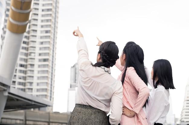 Gruppe von asiatischen geschäftsfrauen, die mit einem lächeln im konzept des arbeitsfortschritts bei der gruppe der weiblichen büroangestellten von outdoorthai nach vorne zeigen.