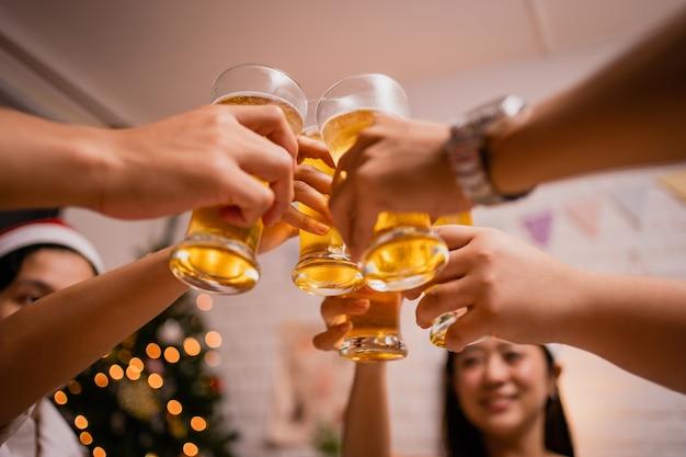 Gruppe von asiatischen leuten klirren gläser an einer party weihnachten zu hause. sie sind sehr glücklich und lustig.