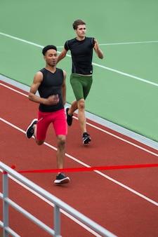 Gruppe von athletenmännern laufen auf laufbahn im freien