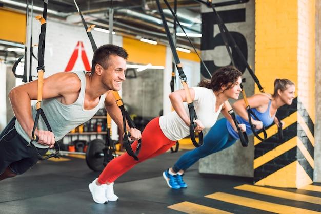 Gruppe von athletischen leuten, die mit eignungsbügel im gesundheitsjungen trainieren