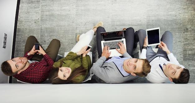 Gruppe von attraktiven jungen leuten, die auf dem boden sitzen und einen laptop, tablet-pc, smartphones verwenden, lächelnd.