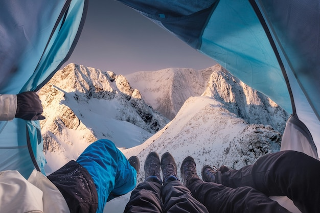Gruppe von bergsteigern sind in einem zelt mit blick auf schneesturm am berg geöffnet