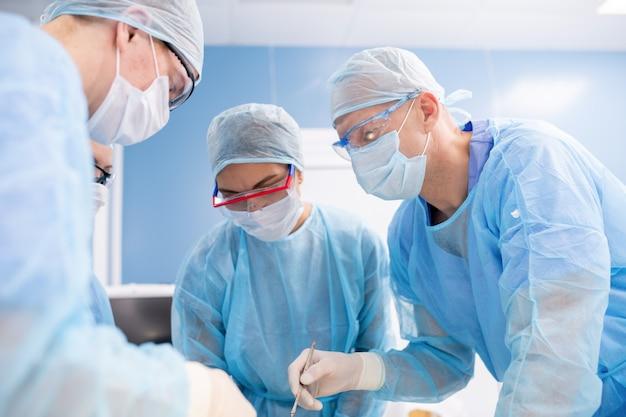 Gruppe von chirurgen in masken, handschuhen und arbeitskleidung, die sich während der operation im krankenhaus über den patienten beugen