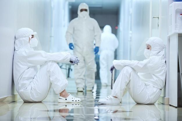 Gruppe von chirurgen in schutzuniformen, die auf dem korridor des krankenhauses sitzen, das sie während der pandemie arbeiten