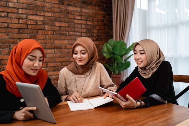 Gruppe von college-studenten, freunde mit digitalem tablet und tragen eines buches