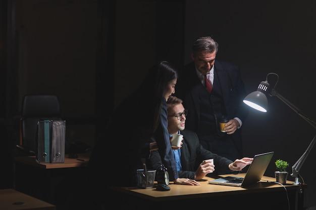 Gruppe von diversity-geschäftsleuten, die nachts spät im büro arbeiten. zwei kaukasische männer und ein asiatisches sekretärin sprechen und diskutieren über ein kreatives projekt mit laptop