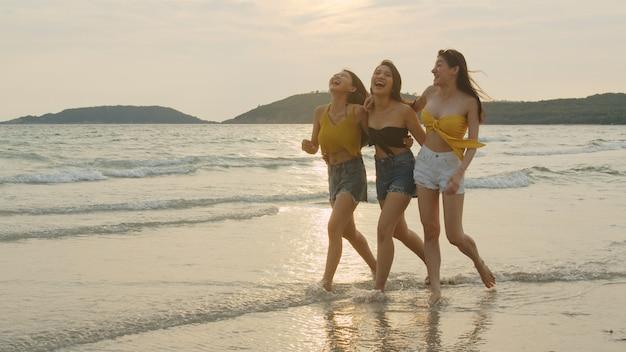 Gruppe von drei asiatischen jungen frauen, die auf strand laufen