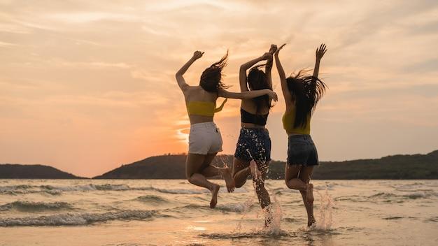 Gruppe von drei asiatischen jungen frauen, die auf strand springen