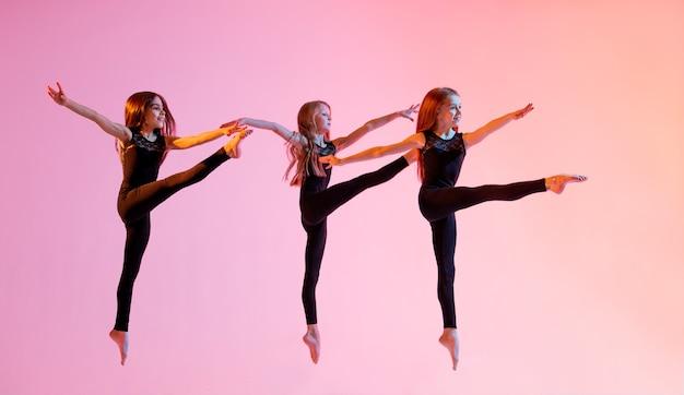 Gruppe von drei ballettmädchen in schwarzen eng anliegenden anzügen, die auf einem roten hintergrund springen