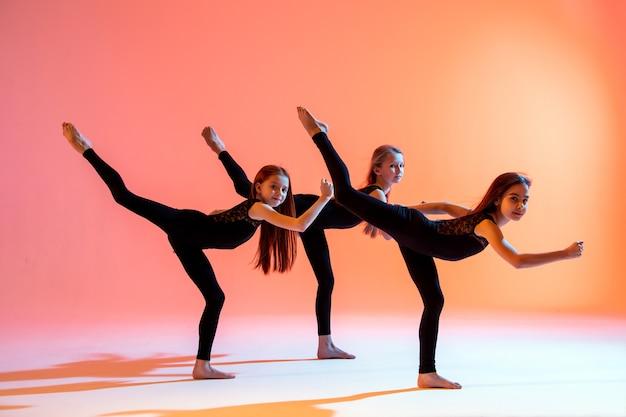 Gruppe von drei ballettmädchen in schwarzen eng anliegenden anzügen, die auf einem roten hintergrund tanzen