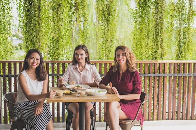 Gruppe von drei besten freunden, die zusammen in einem café zu mittag essen