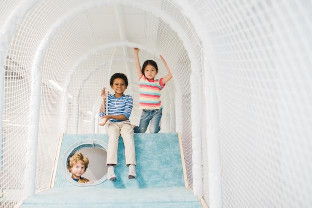 Gruppe von drei entzückenden kindern verschiedener ethnien, die sie beim spielen im freizeitzentrum betrachten