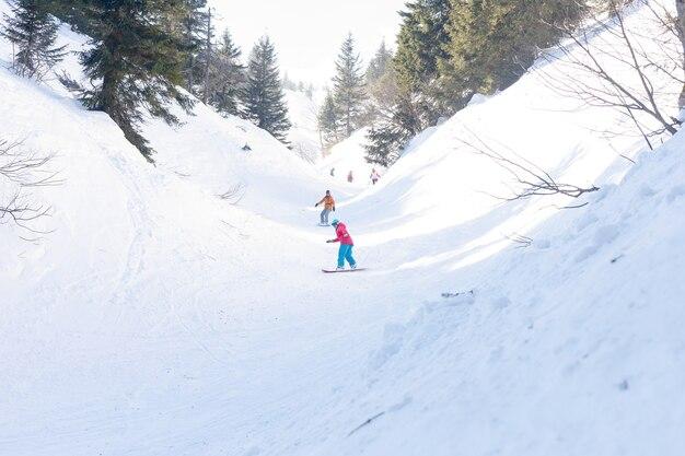 Gruppe von drei freeride-snowboardern, weiblich und männlich, rollt und fährt snowboard auf der schneepiste und genießt die wunderschöne alpenkette im hintergrund. rückansicht.