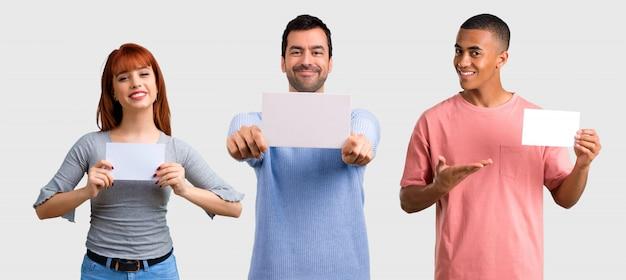 Gruppe von drei freunden, die ein leeres weißes plakat für einsatz halten