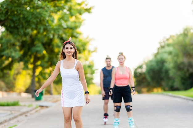 Gruppe von drei freunden, die mit inline-skate in einer straße eines parks skaten
