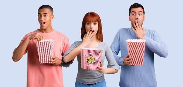 Gruppe von drei freunden, die popcorn essen