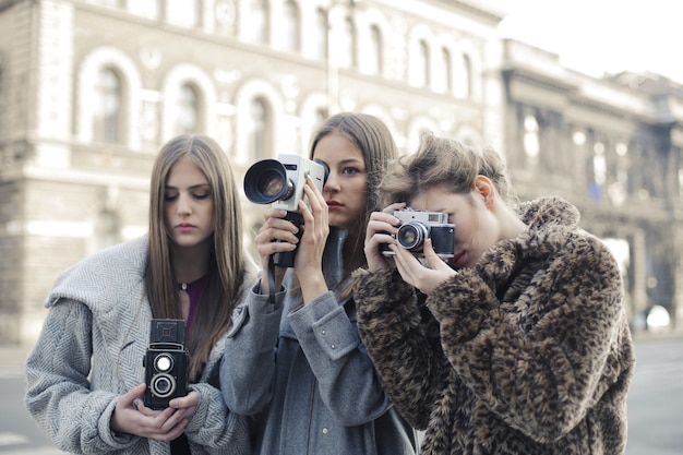 Gruppe von drei freundinnen, die fotos mit ihren kameras machen