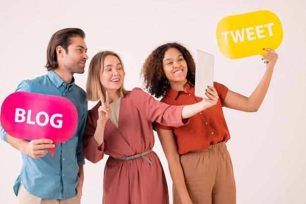 Gruppe von drei fröhlichen, freundlichen millennials, die selfies machen, während zwei von ihnen papierblasen oder symbole aus sozialen netzwerken halten