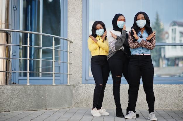 Gruppe von drei jungen afroamerikaner-freiwilligen, die gesichtsmaske im freien tragen. coronavirus-quarantäne und globale pandemie.